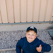 Lapsi istuu maassa ja hymyilee kameralle ja on nostanut peukalon ylöspäin.