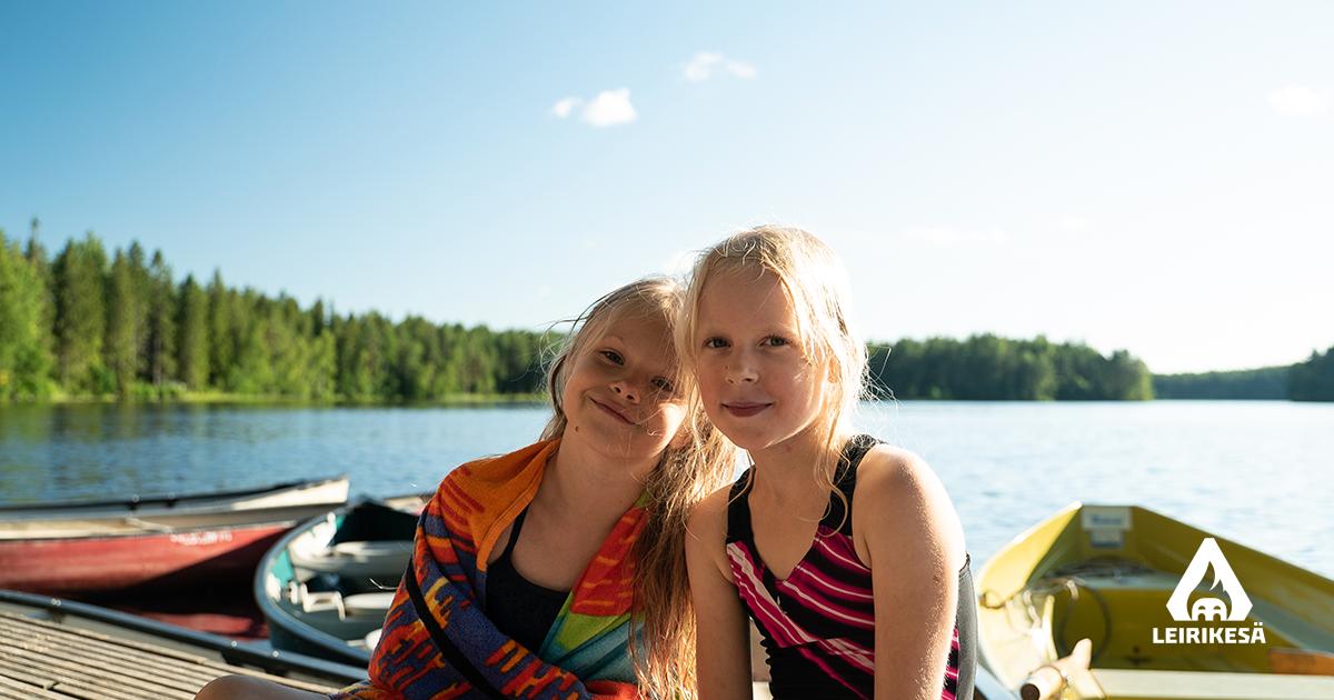Kuvassa kaksi lasta istuvat laiturilla uintireissun jälkeen. Aurinko paistaa taustalta sinisellä taivaalla.