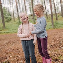 Kaksi lasta nauravat iloisina metsämaastossa.